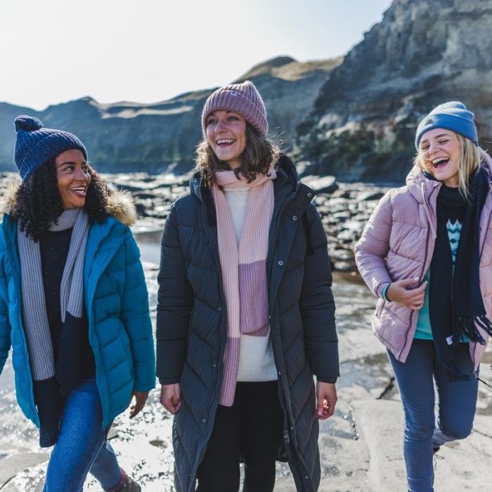 Three women walking outdoors wearing cosy hats and coats